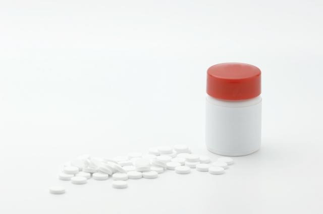 散らばる錠剤 白いボトル 蓋赤い