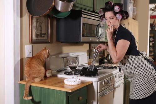猫のそばでタバコを吸いながら料理をする女性