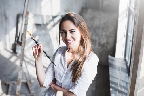筆を持って微笑む女性