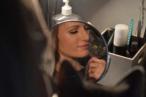 化粧鏡の前で抱かれる猫