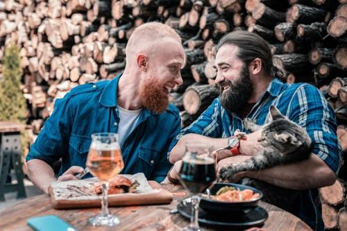 猫を抱きながら食事中の二人の男性