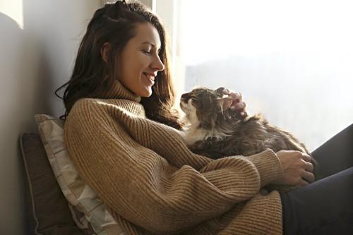 女性の膝の上に乗って撫でられている猫