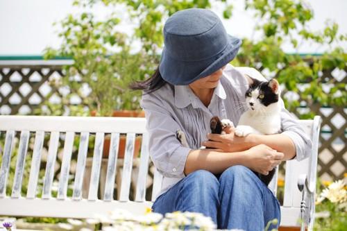 ベンチでくつろぐ女性と猫