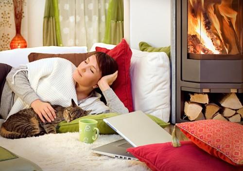 ソファーで一緒に眠る女性と猫
