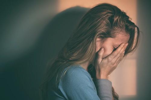 顔を覆って悲しむ女性の横顔