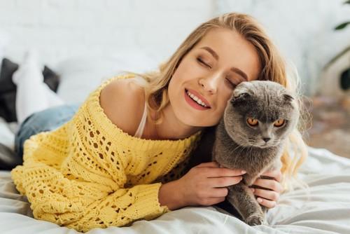 ベッドで女性に抱きつかれて嫌そうな顔をする猫