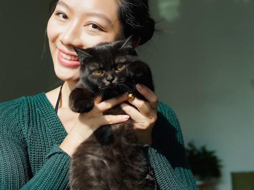 女性に抱き上げられているブリティッシュショートヘアの子猫