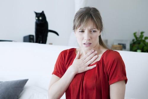 遠くにいる黒猫と苦しそうな女性