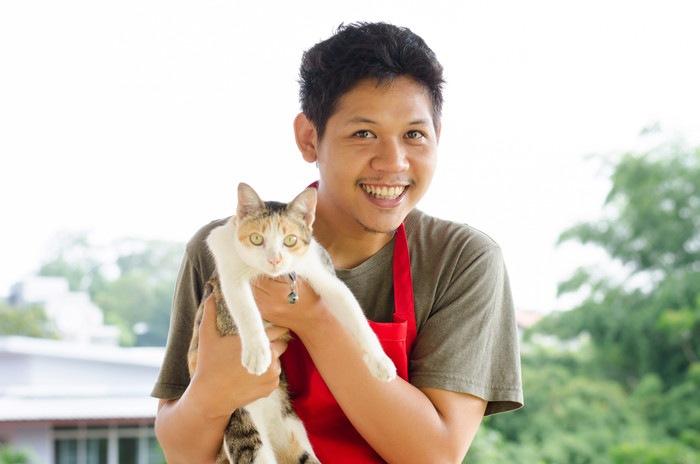 エプロンをつけた男性に抱かれる猫