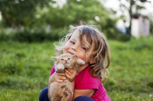 子猫を抱き上げている子供