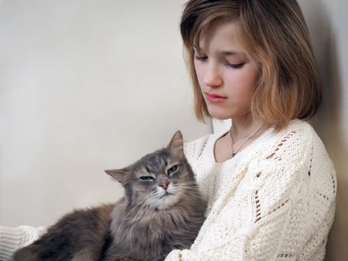 悲しそうな女性と膝の上の猫