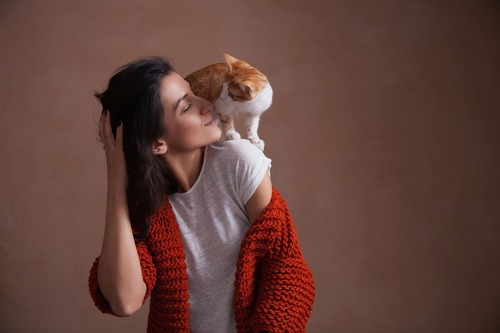 女性の肩に乗りキスをする猫