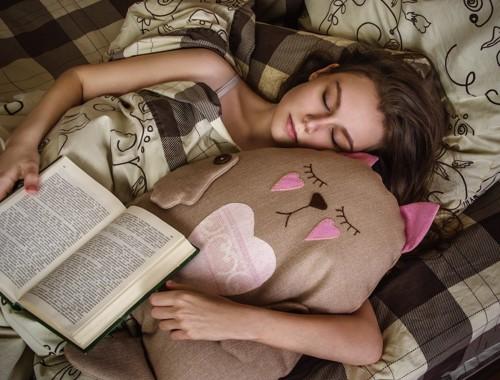 猫のぬいぐるみを抱いて眠る女性