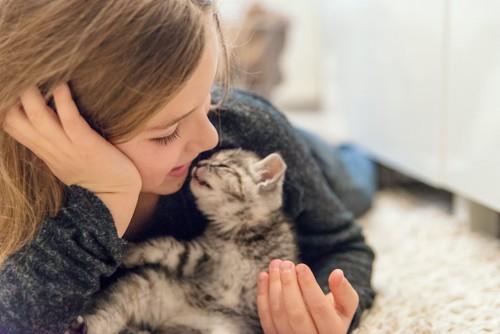 寝転んで顔を近づけ合う少女と子猫