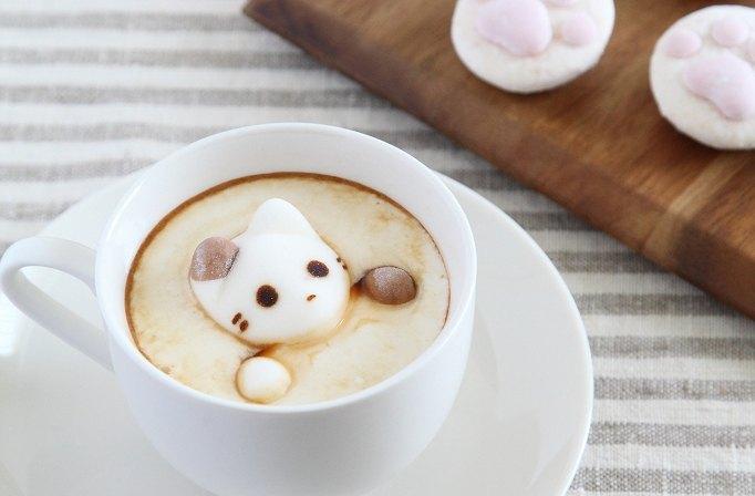 カップの中の猫のマシュマロとトレイの上の肉球のマシュマロ