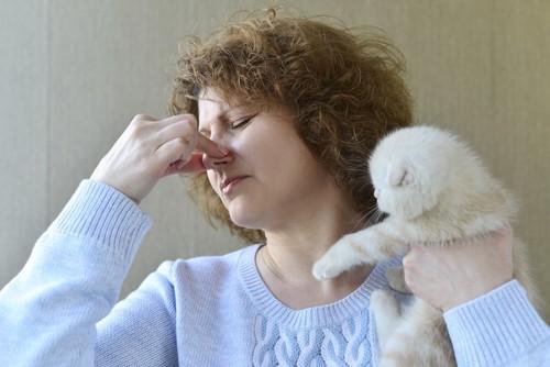 子猫を抱いて鼻をつまむ女性