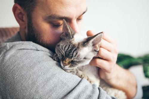 目を閉じて猫を抱きしめる男性