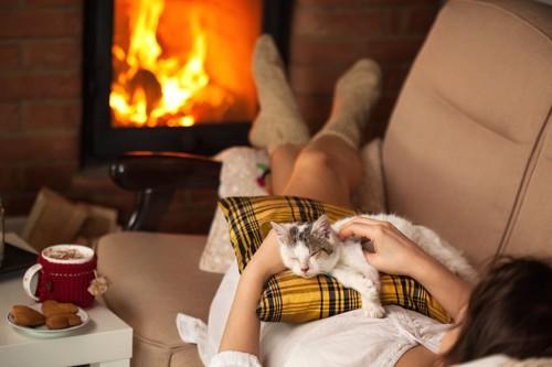暖炉の前のソファーで飼い主と一緒に眠る猫