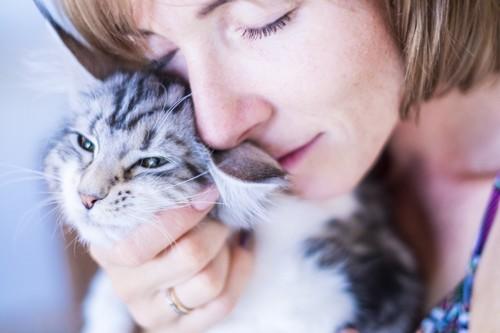 女性に抱きしめられる猫