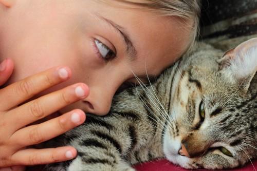女の子と寝る猫