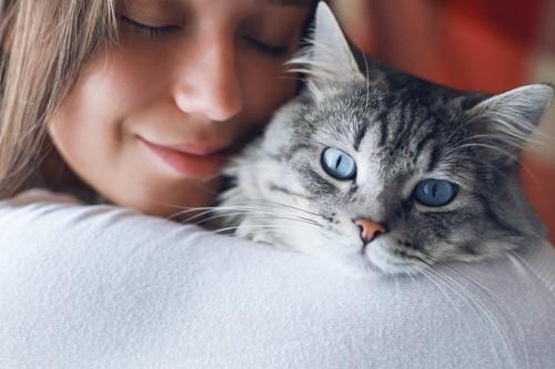 顔を寄り添う人と猫