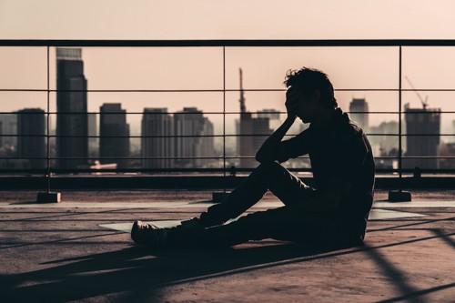 ベランダに座って考え事をしている男性