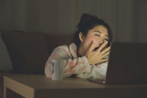 夜更かしをしてパソコンを見る女性