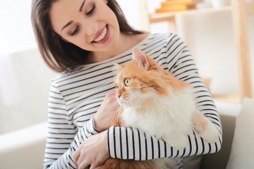 猫を抱っこしている笑顔の女性