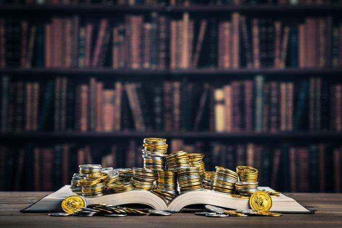 本に積み上がった金貨銀貨