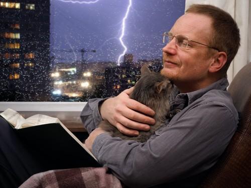 外の雷に怯える猫を優しく抱きしめる男性