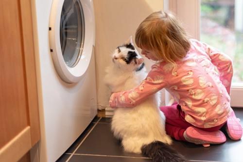洗濯機の前に座る少女と猫