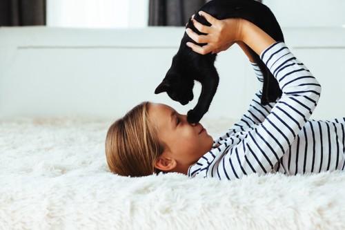 寝転ぶ女の子に抱き上げられる黒猫