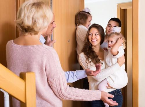赤ちゃんを連れた来客を迎える夫婦