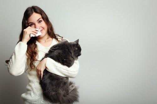 アレルギーのある女性に抱かれる猫