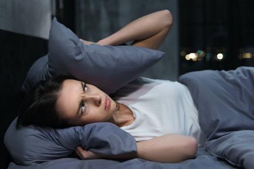 ベッドで横になって枕で耳を抑える女性