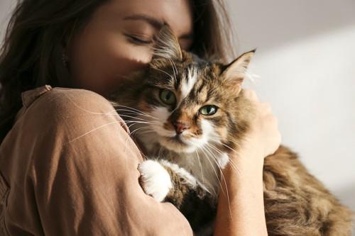 猫を抱っこして目を閉じている女性