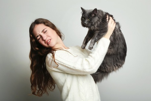 猫を抱っこする猫アレルギー持ちの女性