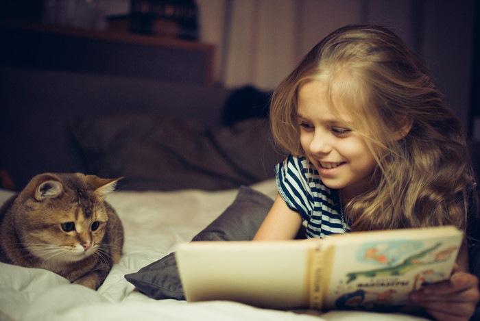 子供が猫に絵本を読み聞かせている