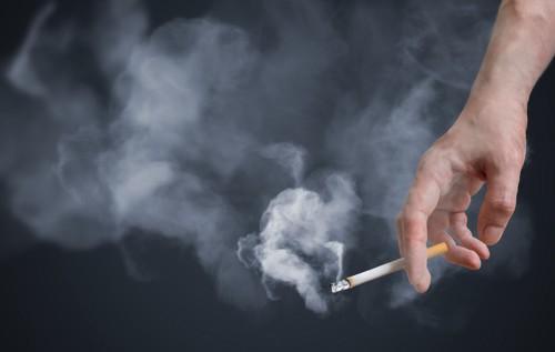 タバコを持った手と煙