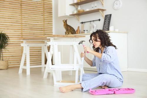 DIYをしている女性と遠くに座る猫