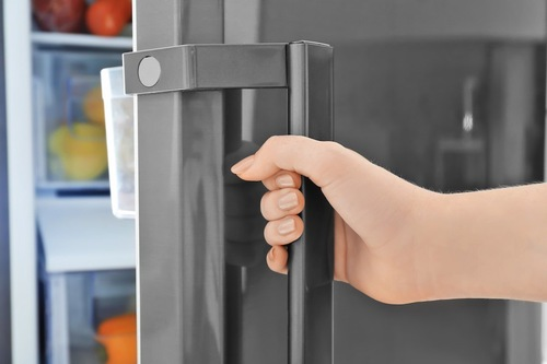 冷蔵庫の扉を閉める人の手