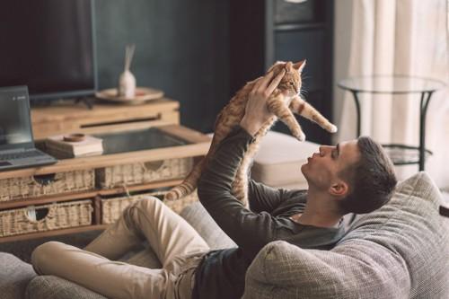 猫を抱き上げる男性