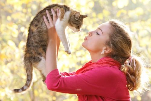 猫を抱き上げてキスをしようとする女性