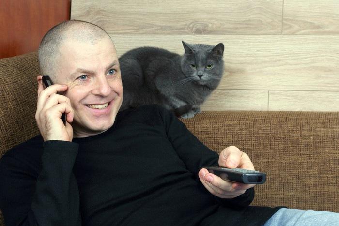 リモコンを持つ男性と猫