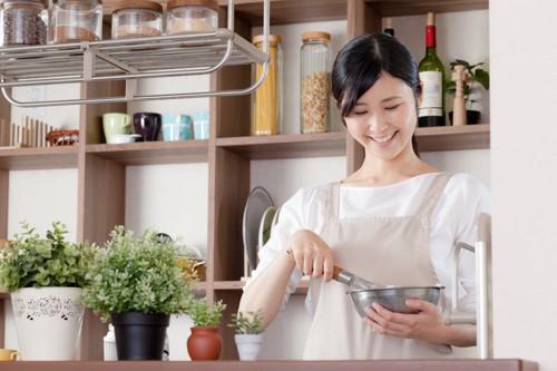 エプロンを着た女性が料理している所