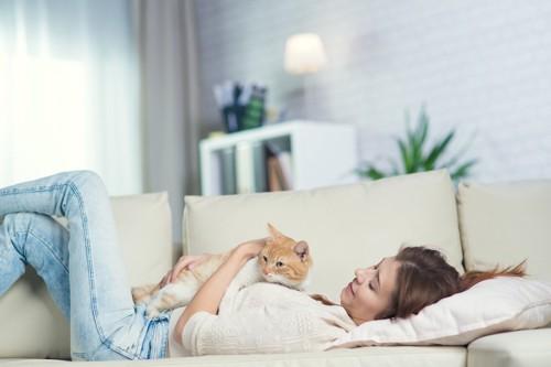ソファーで一緒にくつろぐ女性と猫