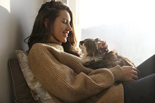 猫を胸の上に乗せて笑顔で撫でる女性