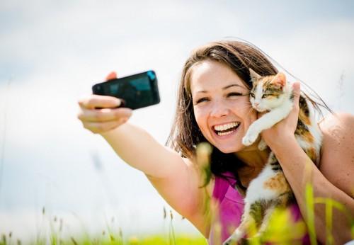 猫と写真を撮る女性