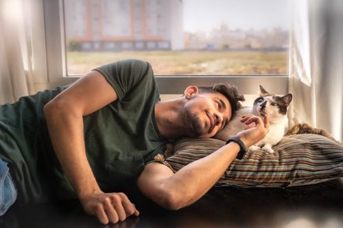 男性に寄りかかれて不満そうな猫