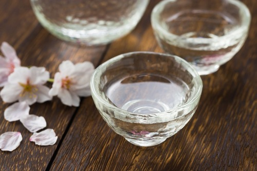 桜の花びらとグラスに入った日本酒